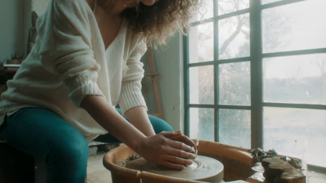 young beautiful woman using pottery wheel at atelier - pottery stock videos & royalty-free footage