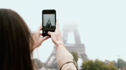 Young beautiful woman walking in Paris, France and taking photos of Eiffel tower in fog on smartphone or mobile phone