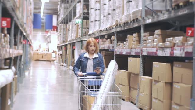 junge schöne frau, die zu fuß durch die hohe regale mit waren in großen aufbau shop und wählen die dinge zu kaufen - möbel stock-videos und b-roll-filmmaterial