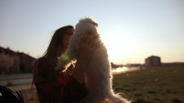 Junge schöne Frau mit langen Haaren umarmt ihren niedlichen maltesischen Hund im Freien