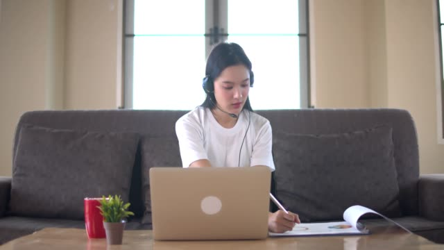 vídeos de stock e filmes b-roll de young beautifull asian woman learning online at home with notebook or tablet sit on brown sofa.quarantine when covid-19 spreading and university close. - aula de formação