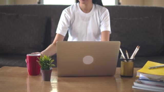 junge schöne asiatische frau lernen online zu hause mit notebook oder tablet sitzen auf braunen sofa.quarantäne, wenn covid-19 verbreitung und universität schließen. - schulische prüfung stock-videos und b-roll-filmmaterial