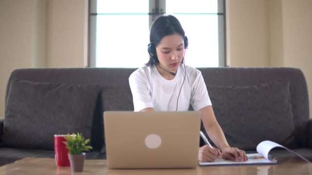 young beautifull asian woman learning online at home with notebook or tablet sit on brown sofa.quarantine when covid-19 spreading and university close. - remote location stock videos & royalty-free footage