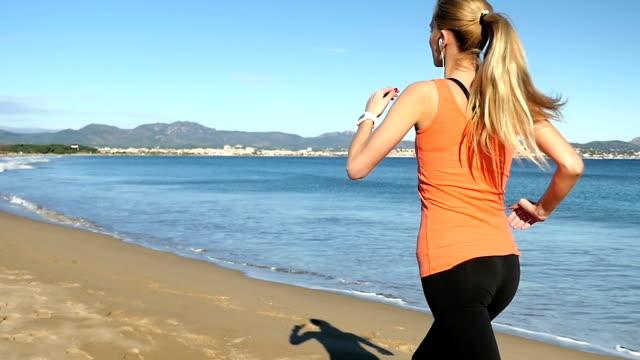 junge schönheit joggen am strand - blondes haar stock-videos und b-roll-filmmaterial
