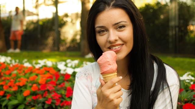 vídeos y material grabado en eventos de stock de mujer joven belleza sonriendo y comiendo helado - helado comida dulce congelada