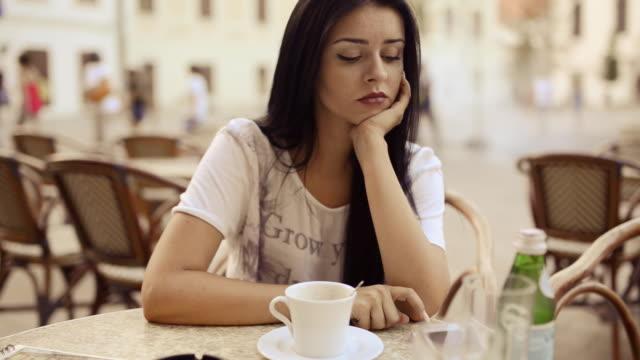 Jeune beauté femme attendant et boire du café au patio.