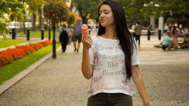 Young beauty woman walking and eating ice cream - SLOW MOTION