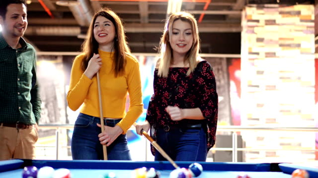 4k young best friends playing billiard with cue and balls on pool table. - pool cue sport stock videos & royalty-free footage