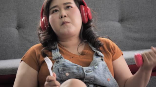 自宅でラップトップ上のヘッドフォンリスニング音楽を身に着けている若い大きなサイズやプラスサイズの女の子。 - 大柄点の映像素材/bロール