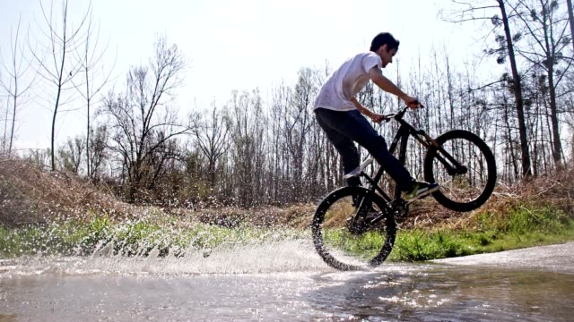 SLO MO Young biker riding wheelie through a puddle