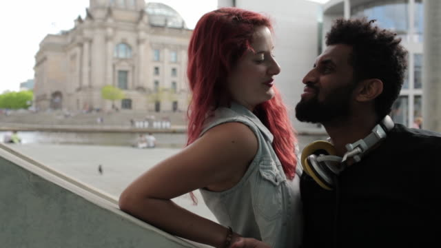Young biracial couple sitting in Berlin's government district, looking at camera, kissing