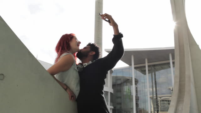 Young biracial couple sitting in Berlin's government district, taking selfie, kissing