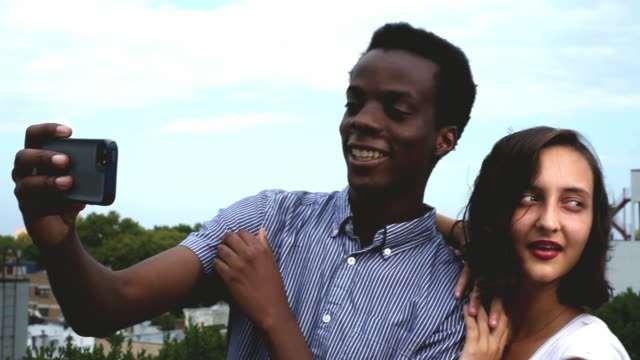 vidéos et rushes de ms young biracial couple taking selfies on apartment building roof - couple d'adolescents