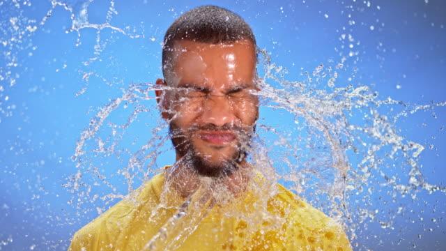slo mo ld biracial jüngling mit einem spritzer wasser mitten ins gesicht geschlagen - vorderansicht stock-videos und b-roll-filmmaterial