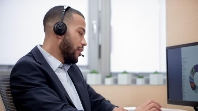 vidéos et rushes de jeune homme biracial dans le centre d'appels aider un client au téléphone - casque téléphonique