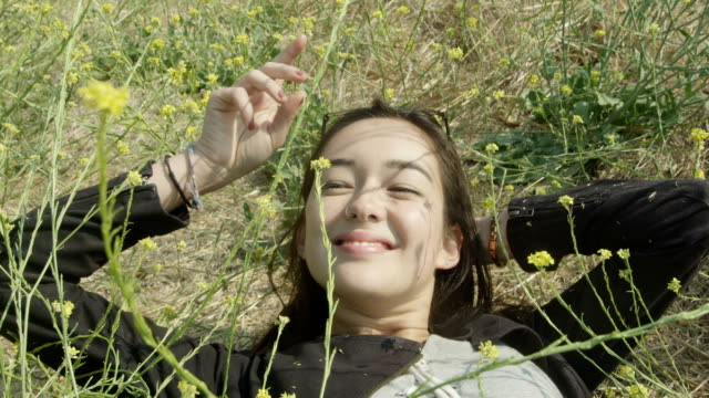 A young bi-racial woman lays in a bed of wildflowers.