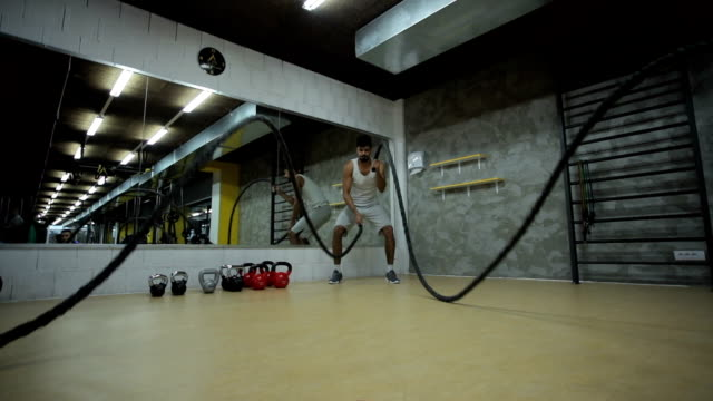 Young black athlete doing battle ropes exercise in a gym. Slow motion.