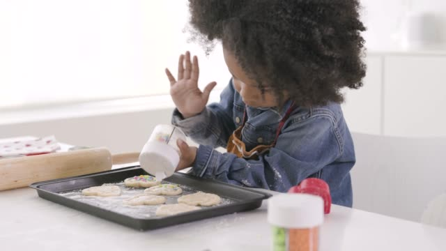 Young black boy baking in kitchen.