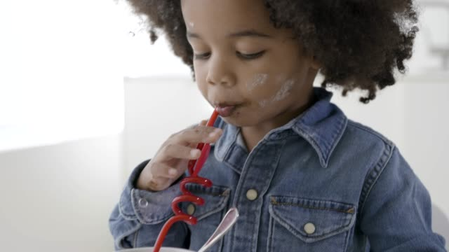 Young black boy drinking from a straw in kitchen.