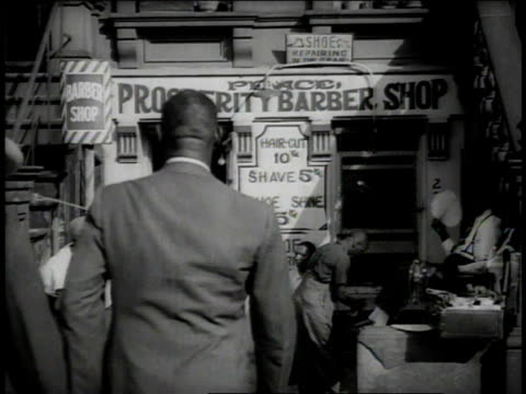 1938 ws young black boys sitting outside prosperity barber shop, one is shining a black man's shoes, two black men in suits go in / new york city, new york, united states - harlem stock videos & royalty-free footage