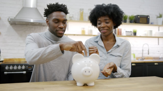 young black couple at home laughing while insetting coins into their piggy bank - piggy bank stock videos & royalty-free footage