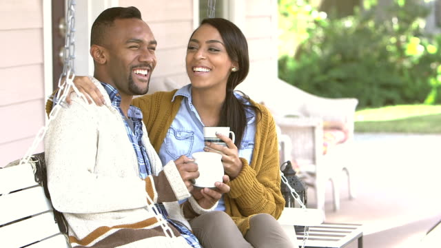Young black couple drinking coffee on porch swing