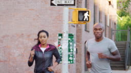 Young black couple jogging in Brooklyn street, close up