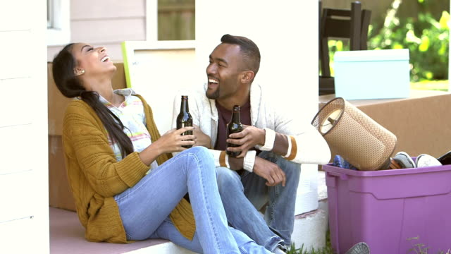Young black couple moving, taking a break, laughing
