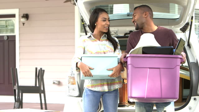 Young black couple moving, unloading car