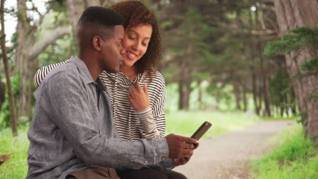 young black couple sit on a park bench looking at their smart phone - sending stock videos and b-roll footage