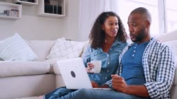 Young black couple sitting on sofa and looking at computer