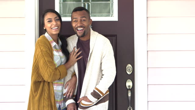 Young black couple standing at front door, smiling