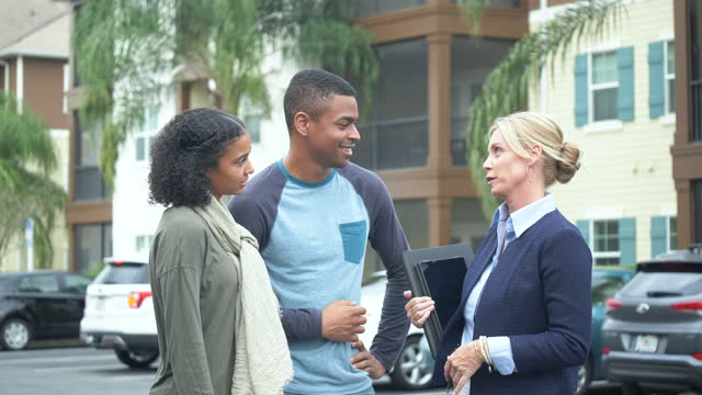 young black couple talking with real estate agent outside building - standing stock videos & royalty-free footage