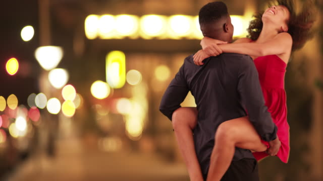 Young black couple twirls around on the city streets