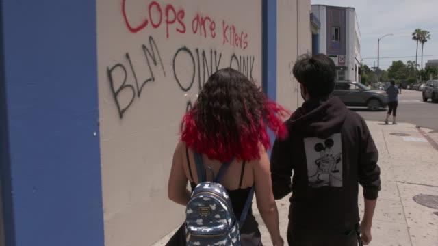 a young black couple walks by graffiti sprayed on a wall the previous night during georgefloydpolicekilling protests in the los angeles fairfax... - young couple stock videos & royalty-free footage
