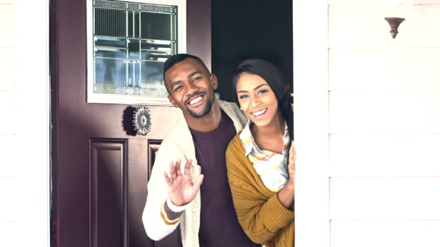 Young black couple welcoming visitors to their home