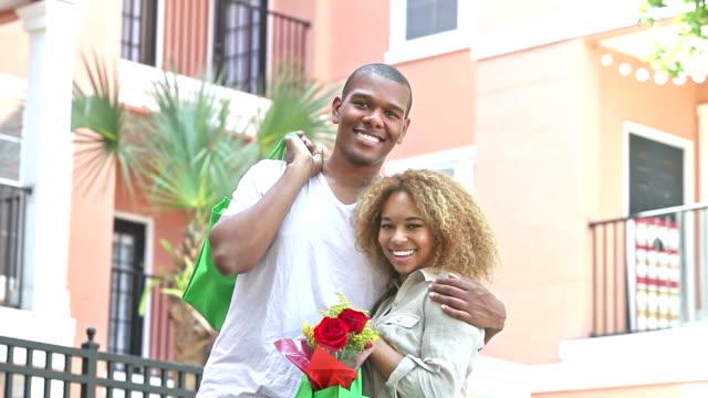 Jeune black couple avec des sacs d'épicerie réutilisables