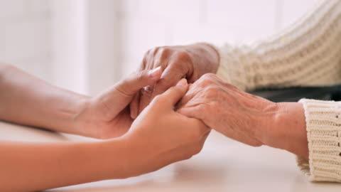 stockvideo's en b-roll-footage met de jonge zwarte vrouwelijke verpleegsterarts houdt hand van hogere grootmoederspatiënt hulp uitdrukkelijke empathie aanmoedigen verteldiagnose bij medisch bezoek thuis. medische, gezondheidszorg, careing, senior care, pensioen, familie, lifestyle, vrijwil - volunteer