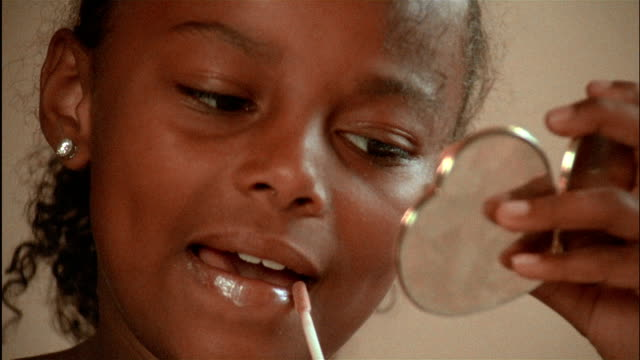 close up young black girl looks in hand mirror while applying lip gloss - lipgloss stock-videos und b-roll-filmmaterial