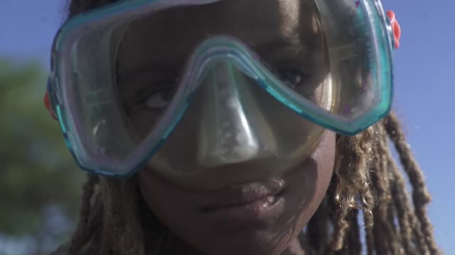 vídeos de stock e filmes b-roll de young black jamaican girl wearing goggles on the beach - povo jamaicano