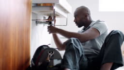 Young black male plumber sitting on the floor and replacing the trap pipe under a bathroom sink, seen from doorway