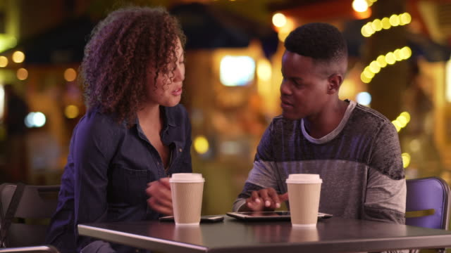 Young black man and woman have coffee at night in the city