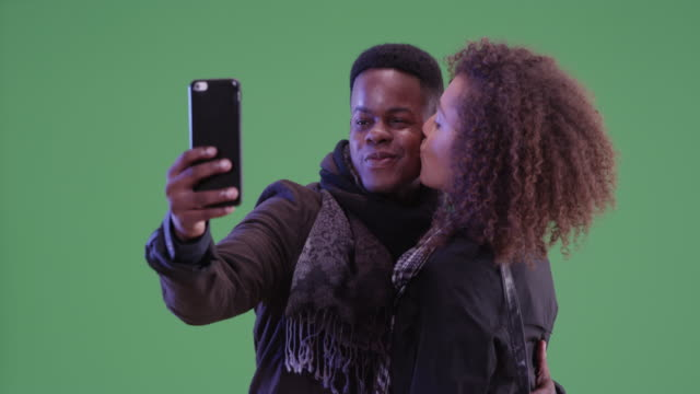 Young black man and woman pose for a selfie on green screen