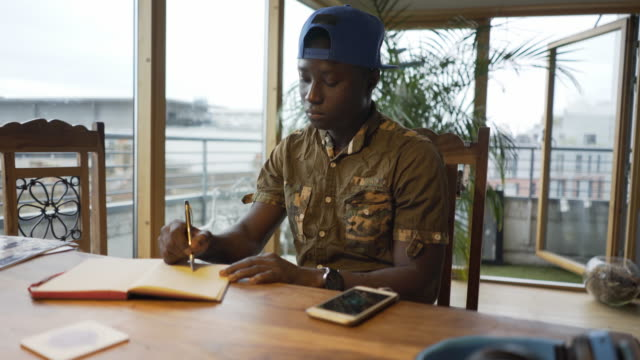 A young black man at his desk writing in a note book.