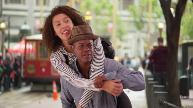 Young black man carries his girlfriend though the streets of San Francisco