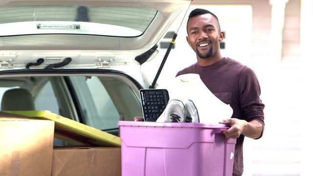 vidéos et rushes de jeune homme noir se déplaçant, de chargement ou de déchargement des voitures - décharger