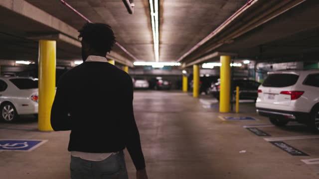 junger schwarzer mann rollt gepäck durch ein parkhaus - parken stock-videos und b-roll-filmmaterial