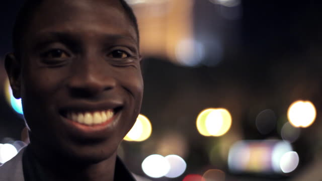 A young Black man smiles as he looks into the camera.