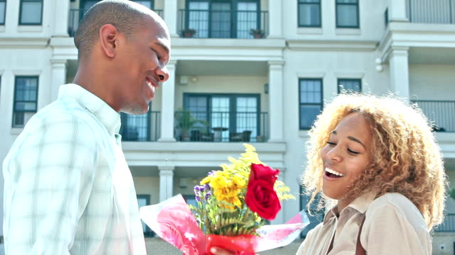 Young black man surprises girlfriend with flowers