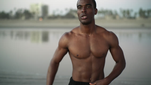 young black man, the well-trained muscular athlete, make body building exercise on the beach at sunset in santa monica, los angeles, california, usa - body building stock videos & royalty-free footage